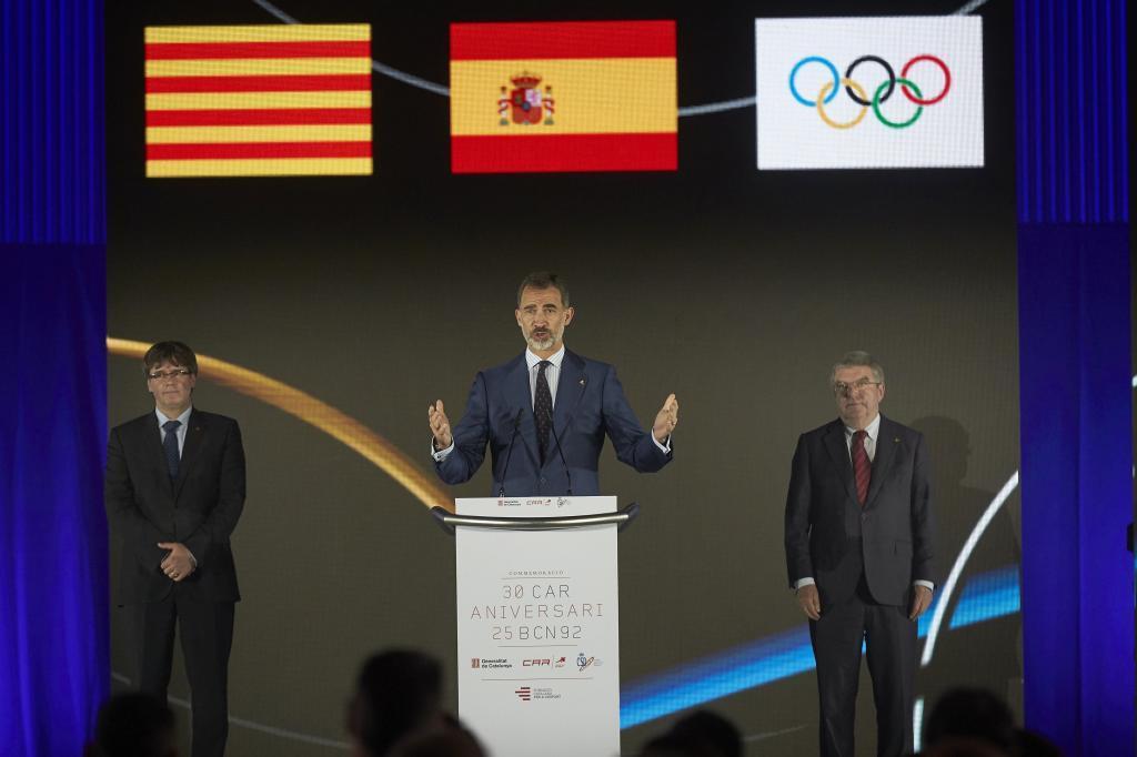 El rey Felipe VI (centro) y el presidente de la Generalitat, Carles Puigdemont (izquierda), junto al presidente del COI, Thomas Bach, en el CAR, donde Su Majestad ha presidido el acto de conmemoración de su XXX Aniversario, enmarcado en el XXV aniversario de Barcelona '92.