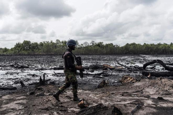 Un hombre camina por una zona abandonada de una refinería de petróleo ilegal.