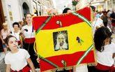 Un grupo folclórico de verdiales sostiene una bandera nacional con...
