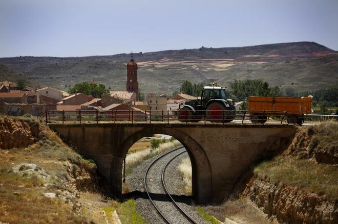 Un tractor cruza el puente sobre la vía del tren de la localidad de...
