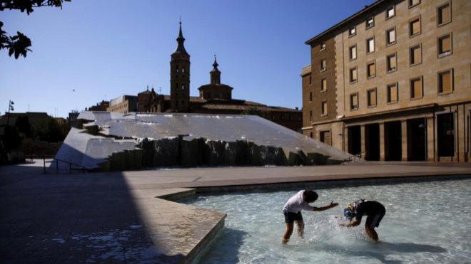 Dos niños juegan en la plaza del Pilar de Zaragoza.