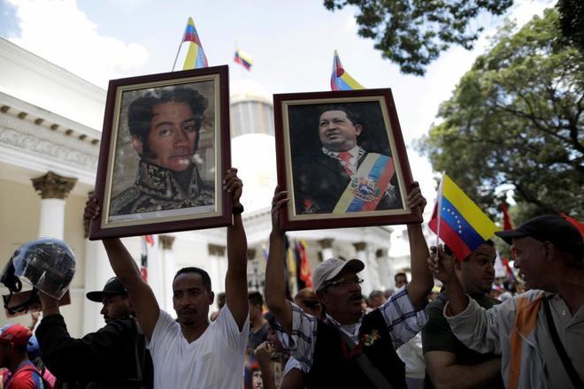 Partidarios de Nicolás Maduro sostienen los retratos de Simón Bolívar (izquierda) y Hugo Chávez (derecha) durante las manifestaciones previas a la toma de poder de la Constituyente