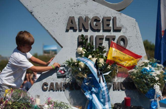 Un niño deja una fotografía en el monumento a Ángel Nieto en el circuito de Jerez.