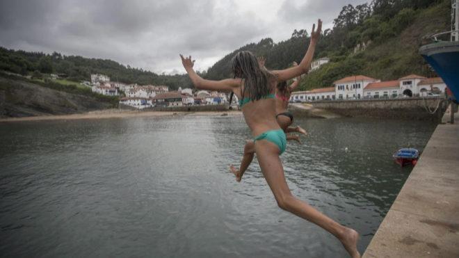 Unas jóvenes se lanzan al agua en el espigón del puerto de Tazones.