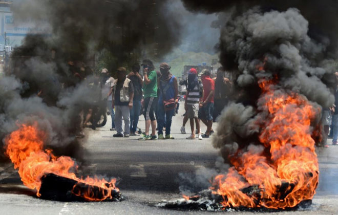 """Anti-government activists stand near a barricade burning in flames in Venezuela's third city, Valencia, on August 6, 2016, a day after a new assembly with supreme powers and loyal to President Nicolas Maduro started functioning in the country. In the video posted online earlier, allegedly at an army base used by the National Bolivarian Armed Forces in Valencia, a man presenting himself as an army captain declared a """"legitimate rebellion... to reject the murderous tyranny of Nicolas Maduro"""" and demanded a transitional government and """"free elections."""" After the video surfaced, military chiefs said troops had put down the """"terrorist"""" attack. / AFP PHOTO / Ronaldo SCHEMIDT"""