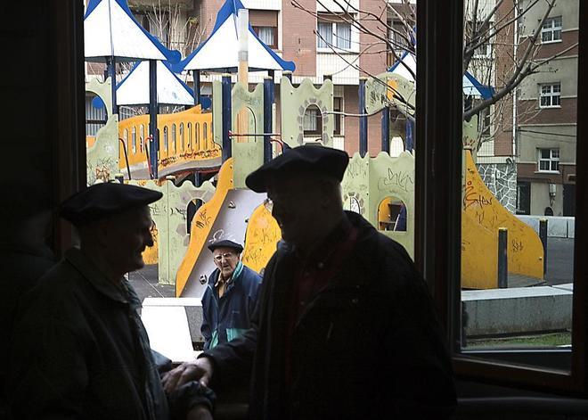 Dos ancianos conversan en un 'hogar del jubilado', con un parque infantil al fondo.