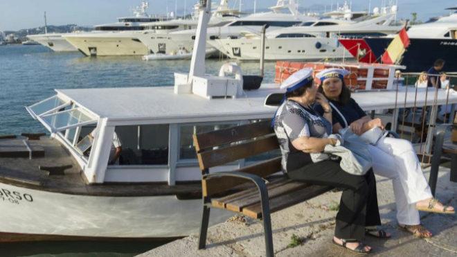 Dos mujeres esperan a que atraque una barca que les lleve a la playa...