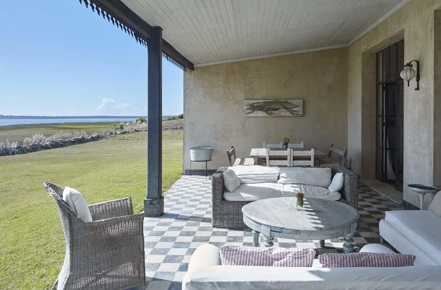 Uno de los porches de la vivienda, con sillones de ratán y mesa...