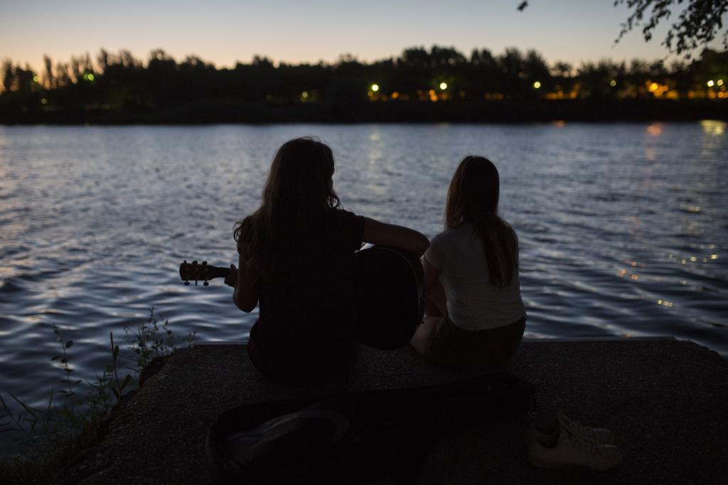Dos jóvenes tocan la guitarra junto al río Duero, al anochecer.