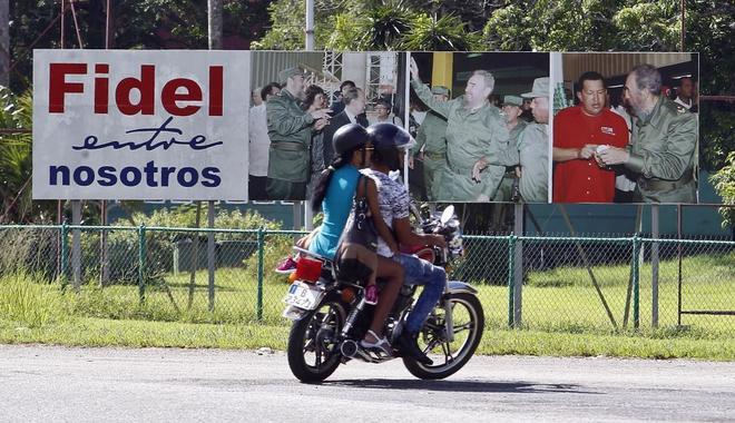 Dos personas en moto pasan junto a un cartel donde aparece el líder de la revolución cubana, Fidel Castro, en La Habana. (Cuba).