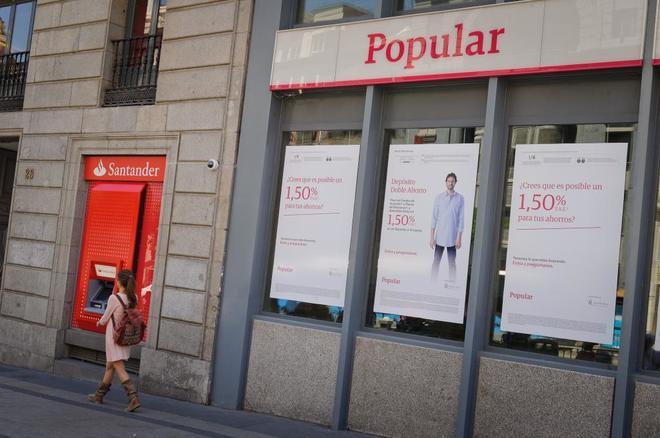 Un cajero de Banco Santander junto a una oficina de Popular.