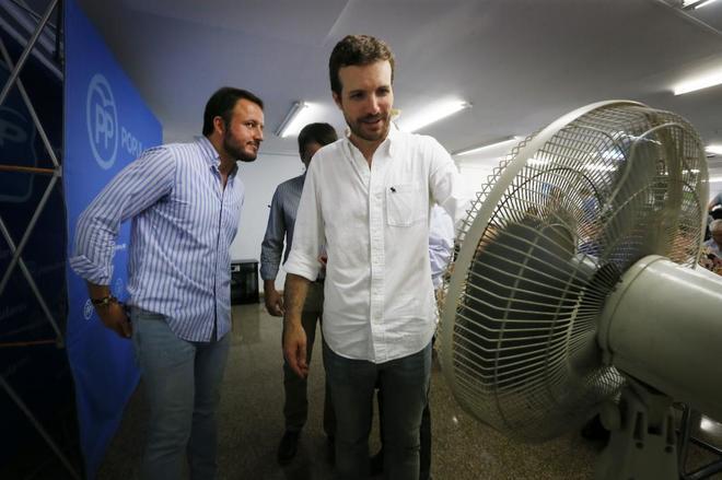 Pablo Ruz mira de soslayo a Pablo Casado que busca un ventilador, ayer en Elche.