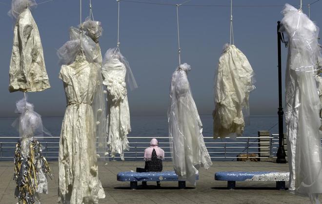 Una mujer, sentada en un banco cerca de una instalación con vestidos de novia de la artista Mireille Honein y la ONG Abaad en la Corniche de Beirut, para denunciar el Código Penal libanés, este abril.