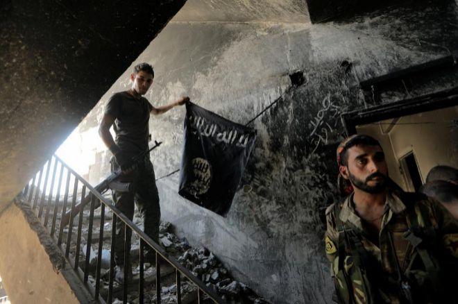Un miembro de las Fuerzas Democráticas Sirias sostiene una bandera del Estado Islámico incautada en Raqqa, Siria.