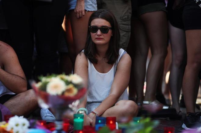 Una mujer, frente al memorial improvisado en recuerdo de las víctimas...