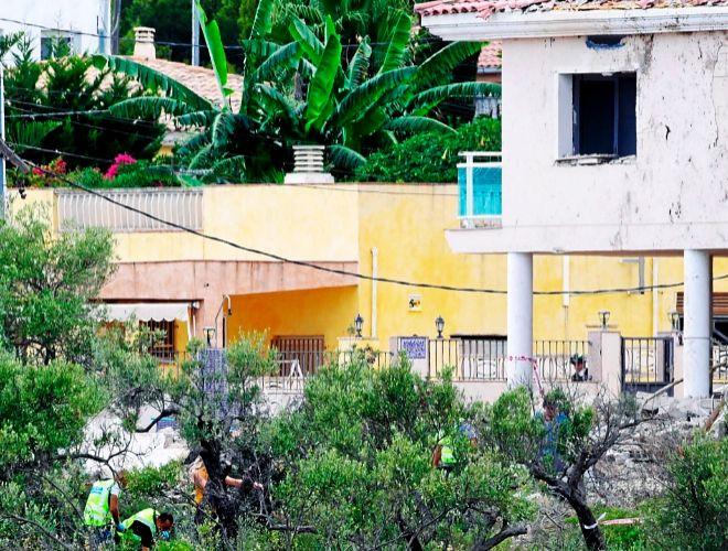 Los investigadores buscan indicios entre los escombros de la casa de...