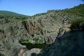 Una excursionista se asoma al borde de la quebrada en cuyo fondo...