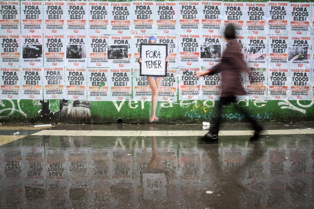 Una persona pasa frente a un muro lleno de carteles contra Michel Temer en la avenida Paulista en Sao Paulo (Brasil).