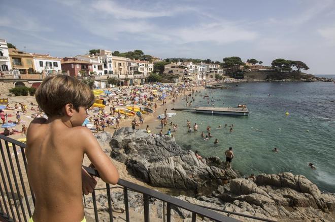 Un niño observa desde una terraza la playa de Canadell, en...