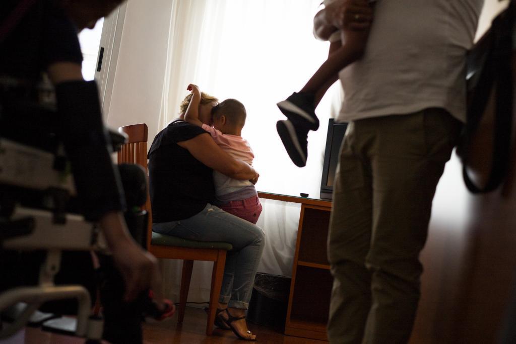 La madre abraza a uno de sus hijos mientras el padre lleva en brazos al más pequeño. A la izquierda, sentado, el mayor de los tres hermanos.