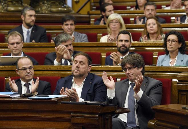 Carles Puigdemont (dcha.) junto a Oriol Junqueras y Jordi Turul aplauden con el resto de la bancada del Junts Pel Sí, ayer en el Parlament.