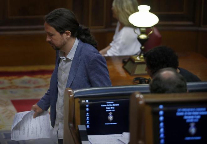 Pablo Iglesias pasa delante de Mariano Rajoy en el pleno del 30 de...