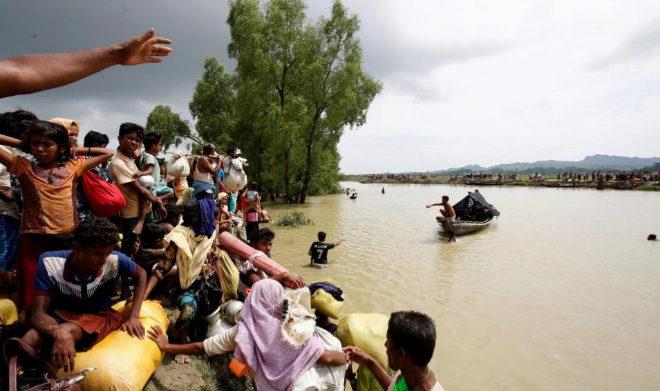 Un grupo de refugiados huyen hacia Bangladesh a través del río Naf.