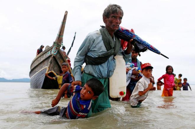 Un refugiado rohingya lleva a un niño tras cruzar la frontera entre Bangladesh y Birmania en barco.
