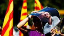 Un hombre se tapa del sol con una imagen de Pablo Iglesias, ayer en la...