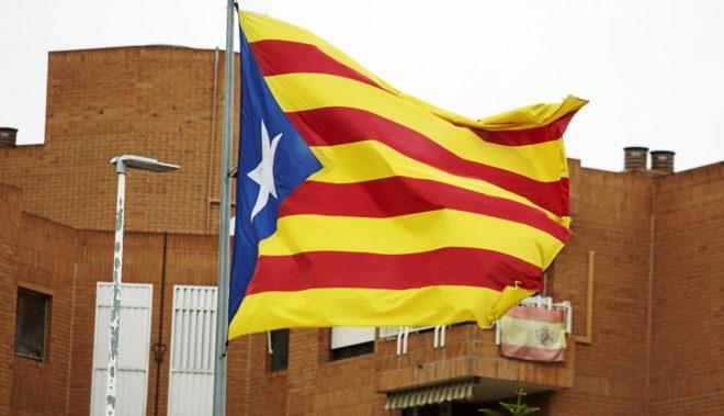 Una bandera estelada ondea al viento ante una bandera española, que...