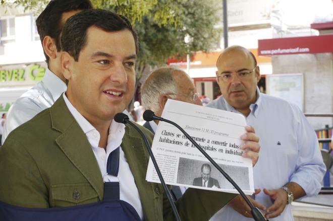 Moreno muestra una información de EL MUNDO sobre las promesas incumplidas en sanidad.