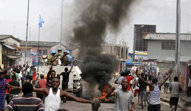 Congoleños protestan contra el presidente Kabila ante la mirada de las fuerzas de la ONU, el pasado diciembre en Kinsasa.