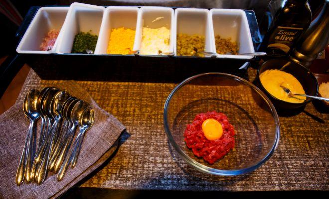 El steak tartare de Lakasa listo para ser aderezado en la mesa frente...