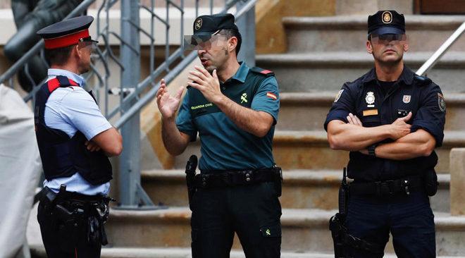 Agentes de Guardia Civil, Mossos y Policía hacen guardia frente a la...