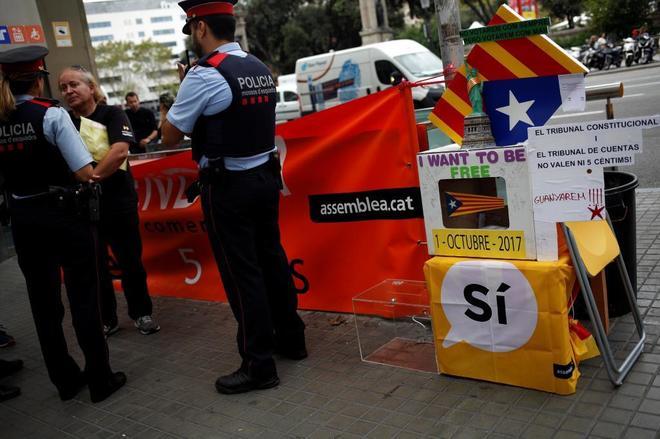 Dos agentes de los Mossos en un puesto pro referéndum a pie de calle.