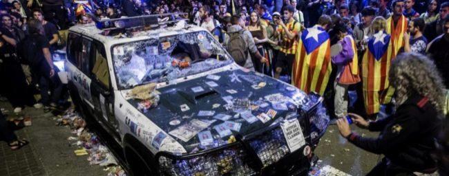Un vehículo de la Guardia Civil destrozado durante los incidentes...