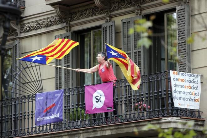 Una mujer ondea las banderas independentistas durante la...