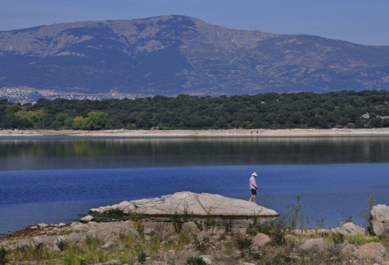 Un pescador en la orilla del embalse de Valmayor, con los Montes de El...