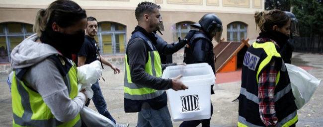 Agentes de la Policía Nacional retiran urnas y papelestas del colegio...