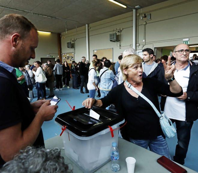 Una mujer hace el gesto de la victoria al votar en un centro...