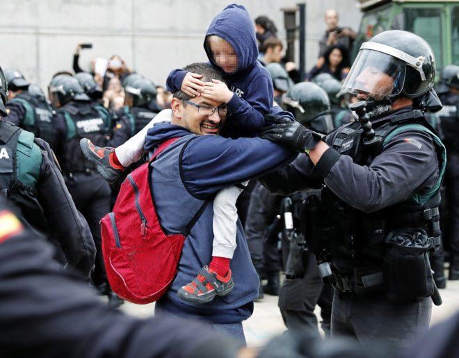 Un guardia civil trata cuidadosamente de que un padre saque a su hijo...