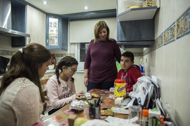 Una madre con sus tres hijos en la cocina de casa.