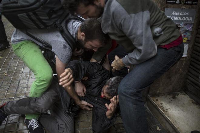 Un hombre herido recibe ayuda de otros tras un enfrentamiento con policías en el colegio Ramón Llull de Barcelona.