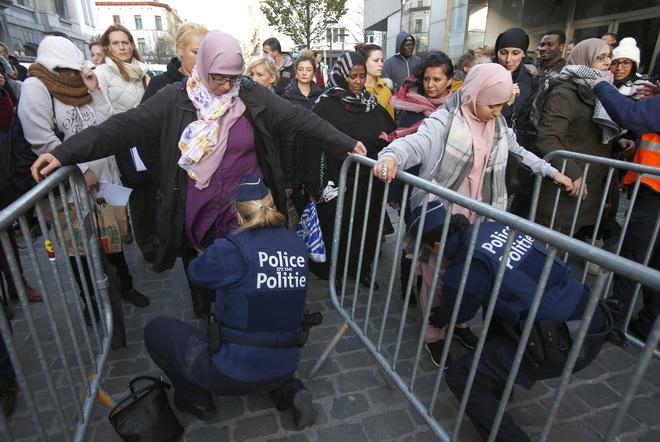 Residentes del suburbio de Bruselas Molenbeek son requisados por la policía.