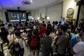 Varias personas escuchan el discurso del Rey en Barcelona.