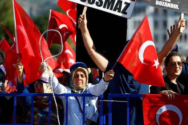 """Simpatizantes del presidente Erdogan ondean banderas turcas durante el juicio a los """"golpistas""""."""