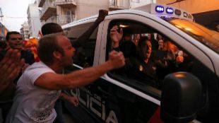 Agentes de la Policía Nacional, animados por varias personas en...