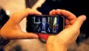 Un hombre escucha a través de su móvil el discurso del Rey sobre la...
