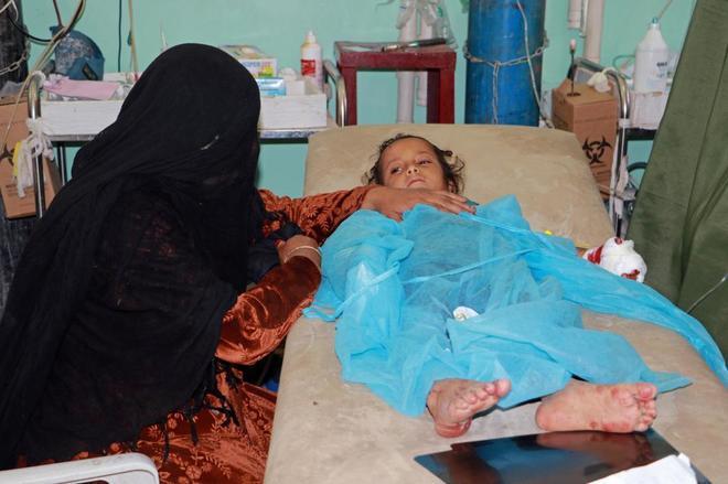 Una mujer se sienta junto a su hija que fue herida durante un ataque aéreo saudí en Saada, Yemen.