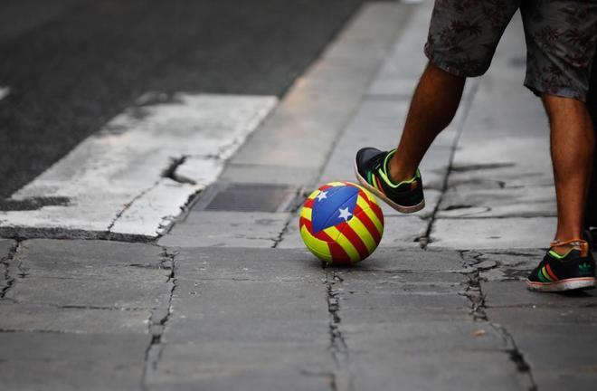 Un joven con un balon con una estelada en la plaza Sant Jaume.